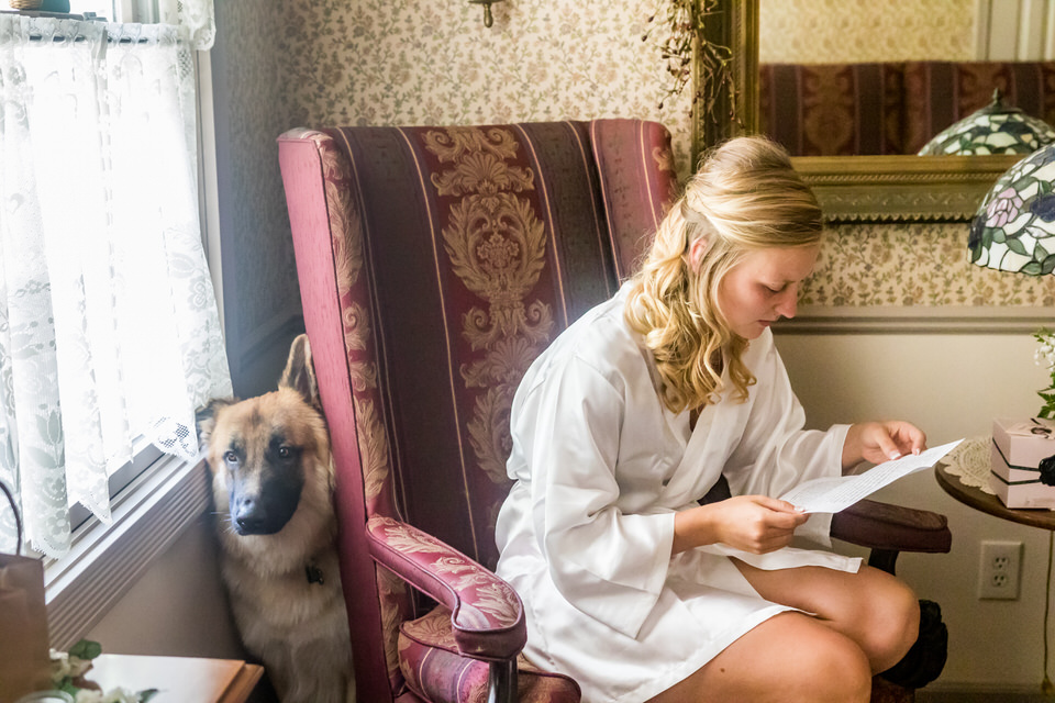 A bride reads a letter from her groom before getting ready for her wedding ceremony