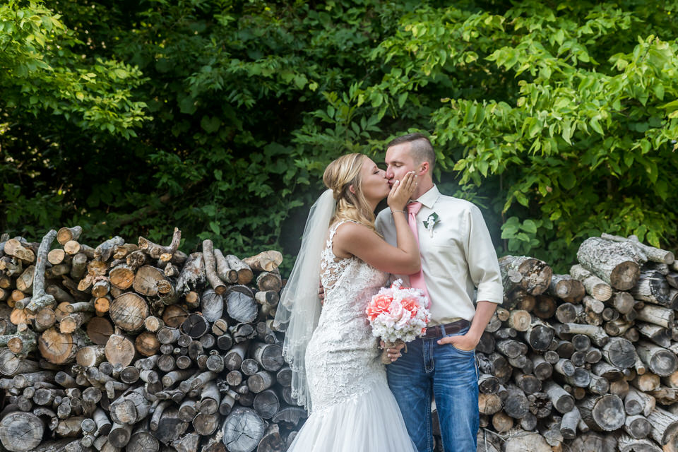 The bride and groom pose for a photo in front of a wood pile at Bridgeton Barn