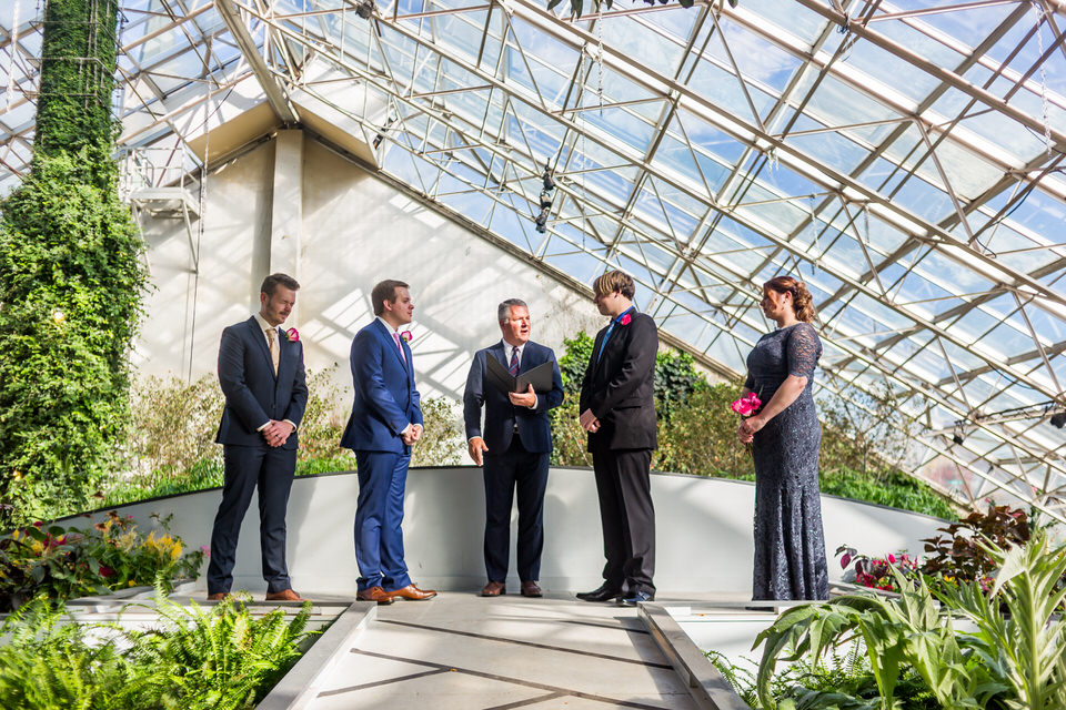 Two grooms say their vows during their wedding ceremony at the Fort Wayne Botanical Gardens