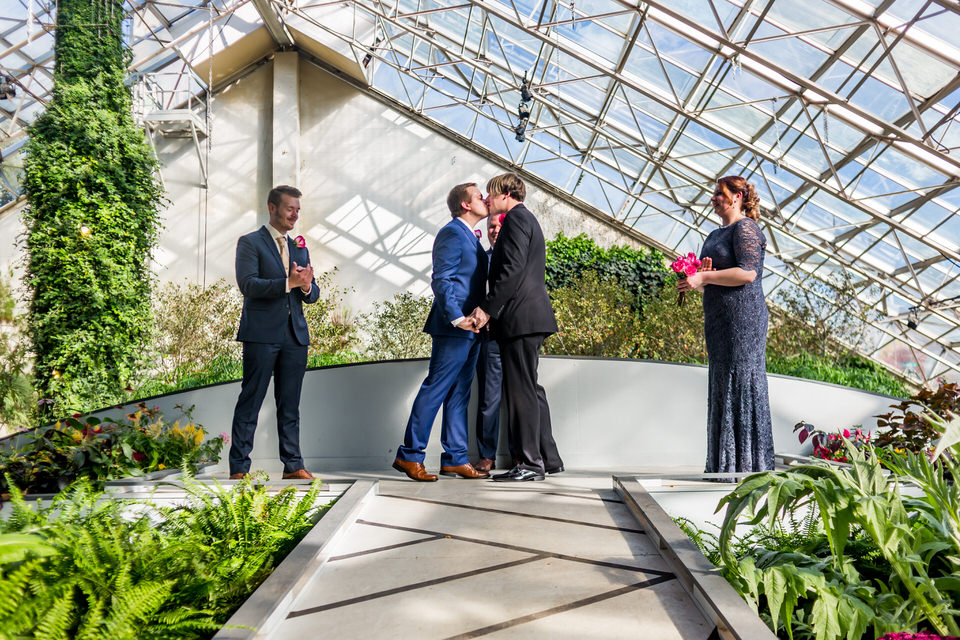 Two grooms share their first kiss as husband and husband at the Botanical Gardens in Fort Wayne, Indiana