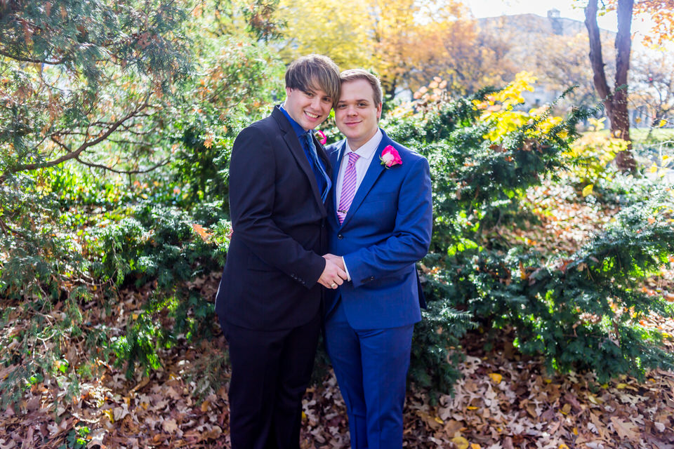 Two grooms stand together for wedding photos at the Fort Wayne Botanical Gardens