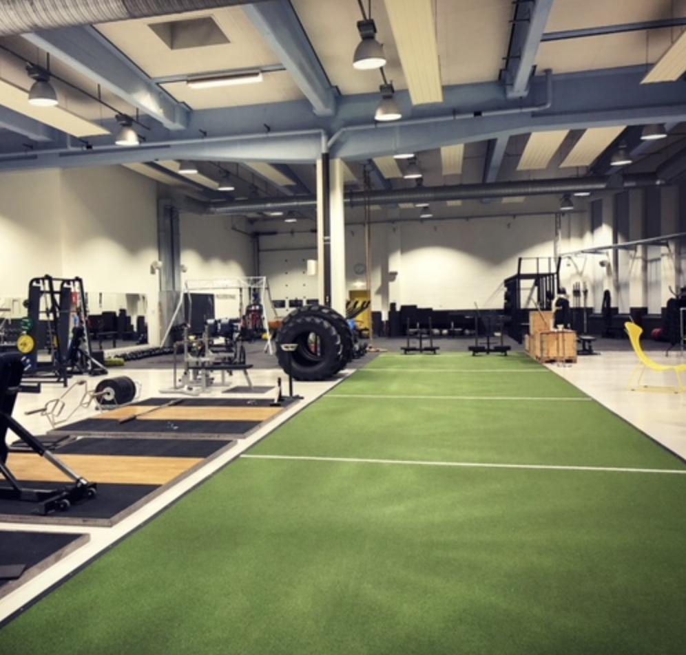"""Konditionsbana för olika typer av uthållighetsträning   """"Parken"""" ligger i mitten av gymmet och kan med fördel användas för både lätt och tung konditionsträning.  Mattan är 23m lång och 4m bred. De vita streckan har 5m mellan sig (1,5m startzon per kant).  Här jobbar vi ofta med slädarna, kroppsvikt (tex utfall eller heklkroppsövningar) eller strong(wo)manutrustning.   Utrustning;  2st slädar Strength Shop 3st däck ca 100-250kg 2st handtag till Farmers Walk 1st sandsäck, upp till 50kg   1st ok, 40kg OBS! """"FÖTTERNA"""" SKADAR LÄTT MATTAN"""