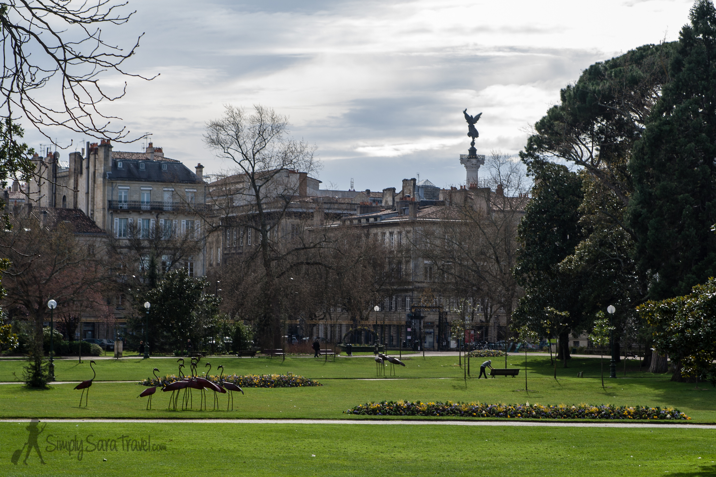 The public garden with a view of theMonument aux Girondins rising up behind the buildings