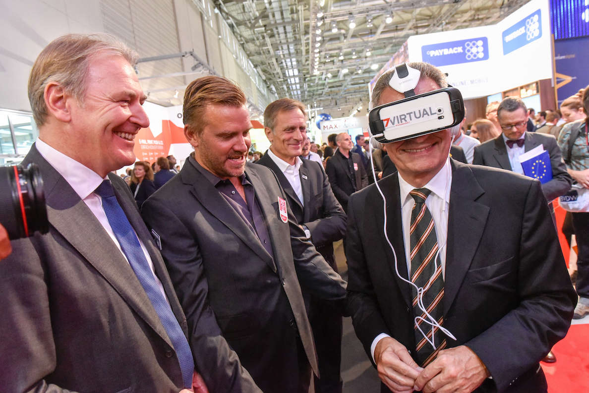 Oettinger (hier rechts im Bild. Aber NICHT der Kerl mit der Europa-Mappe. Sondern mit der Virtual Reality Brille auf dem Kopf. Quelle: dmexco.de)