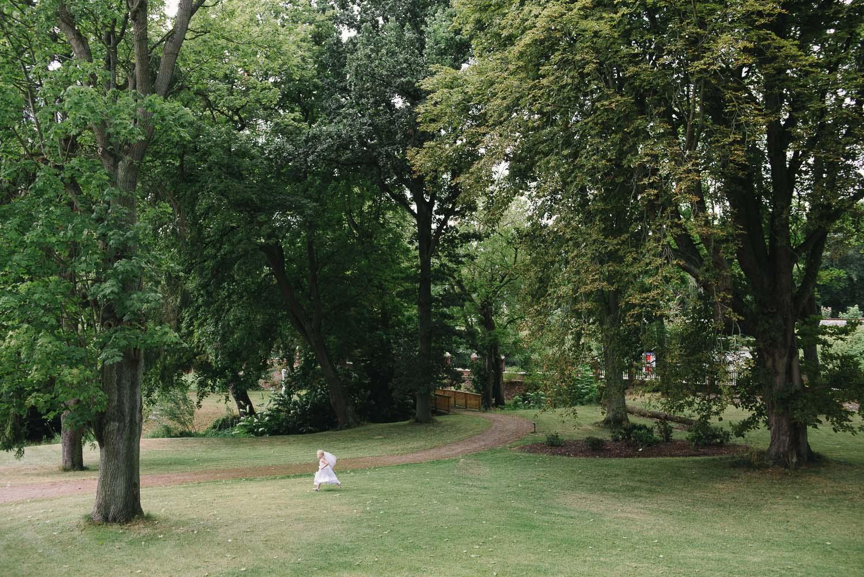 Junge trifft Mädchen Hochzeitsfotografie - Blumenkind während einer Hochzeit im Park der Villa Papendorf