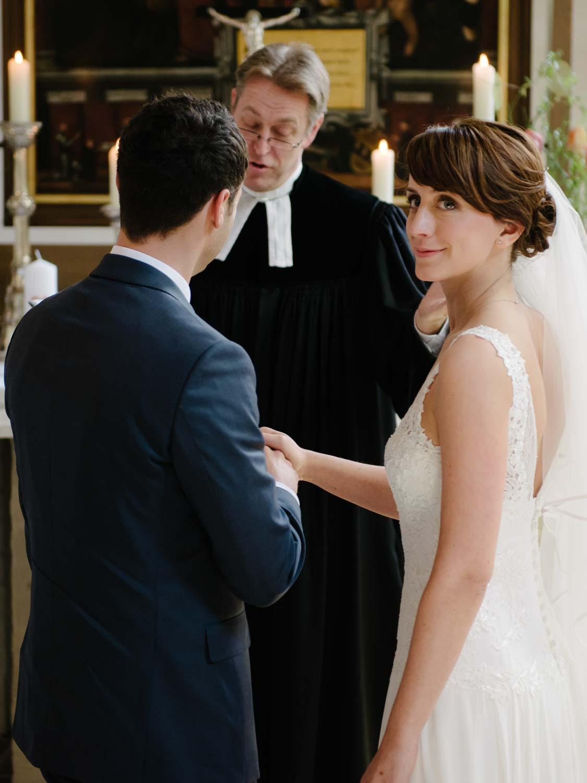 Braut schaut dem Kirchenchor zu kirchliche Trauung Hochzeit Rostocker Fotograf in Augsburg