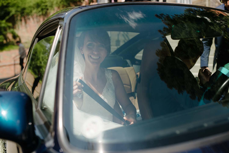 Braut im Hochzeitsauto lachend durch das Fenster fotografiert Hochzeit Rostocker Fotograf in Augsburg