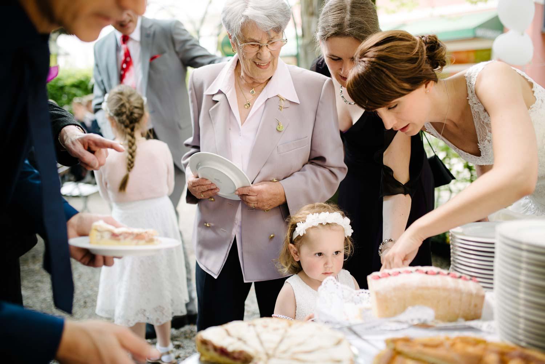 Kinden und Hochzeitsgäste bekommen von der Braut ein stück Kuchen Kaffee Kuchen Hochzeit Rostocker Fotograf in Augsburg