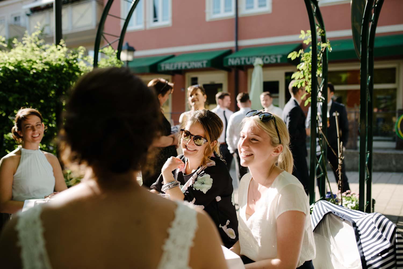 Braut und Gäste lachen bei Kaffee Kuchen Hochzeit Rostocker Fotograf in Augsburg