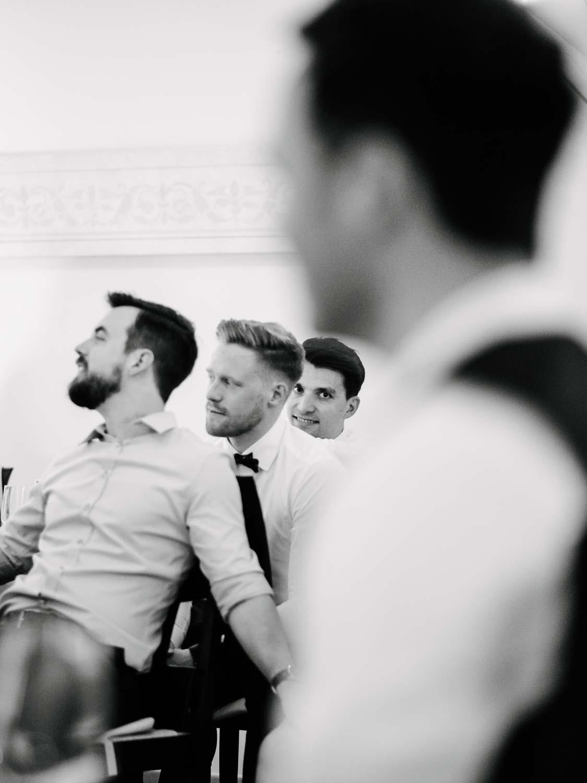 Best Men lachen Bräutigam im Vordergrund unscharf Hochzeit Rostocker Fotograf in Augsburg