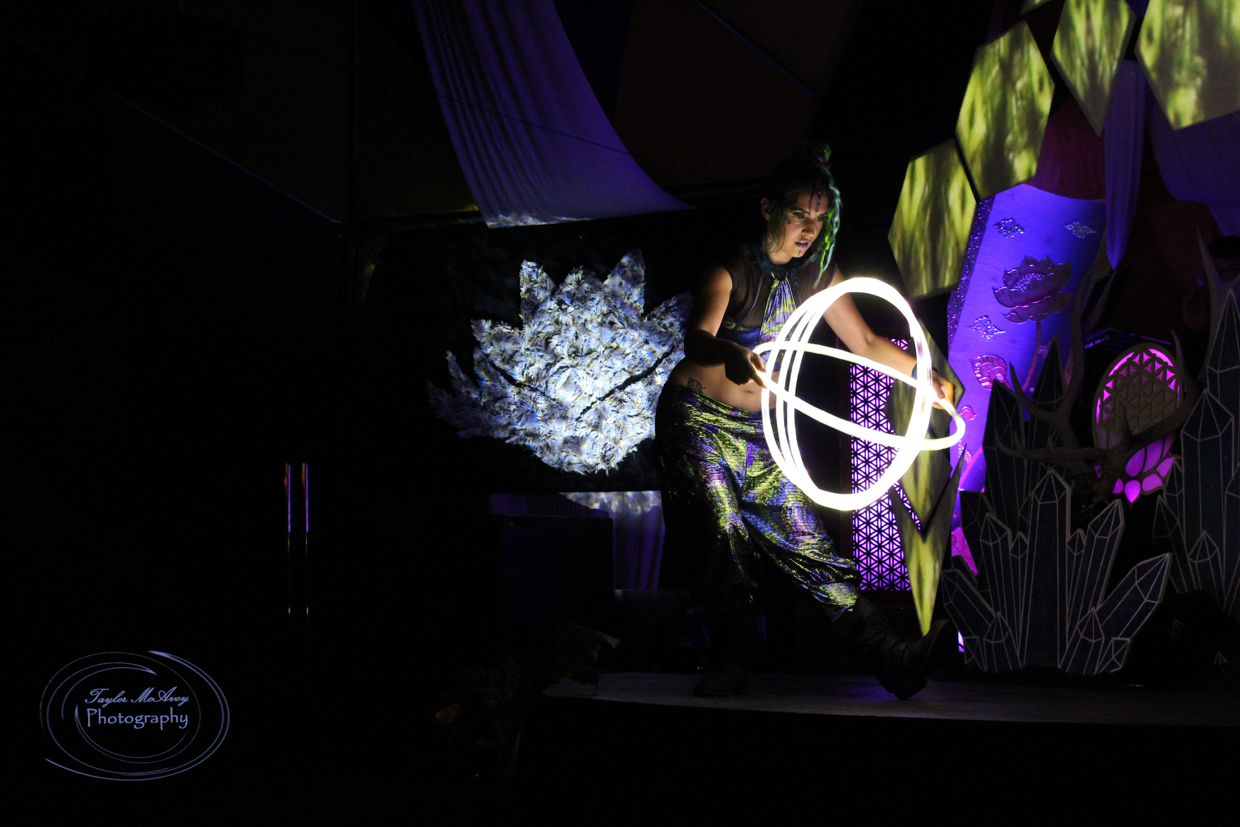 Performer Luma dances her hoop routine with four lighted hoops on stage before the dance floor in the Dream Dome.