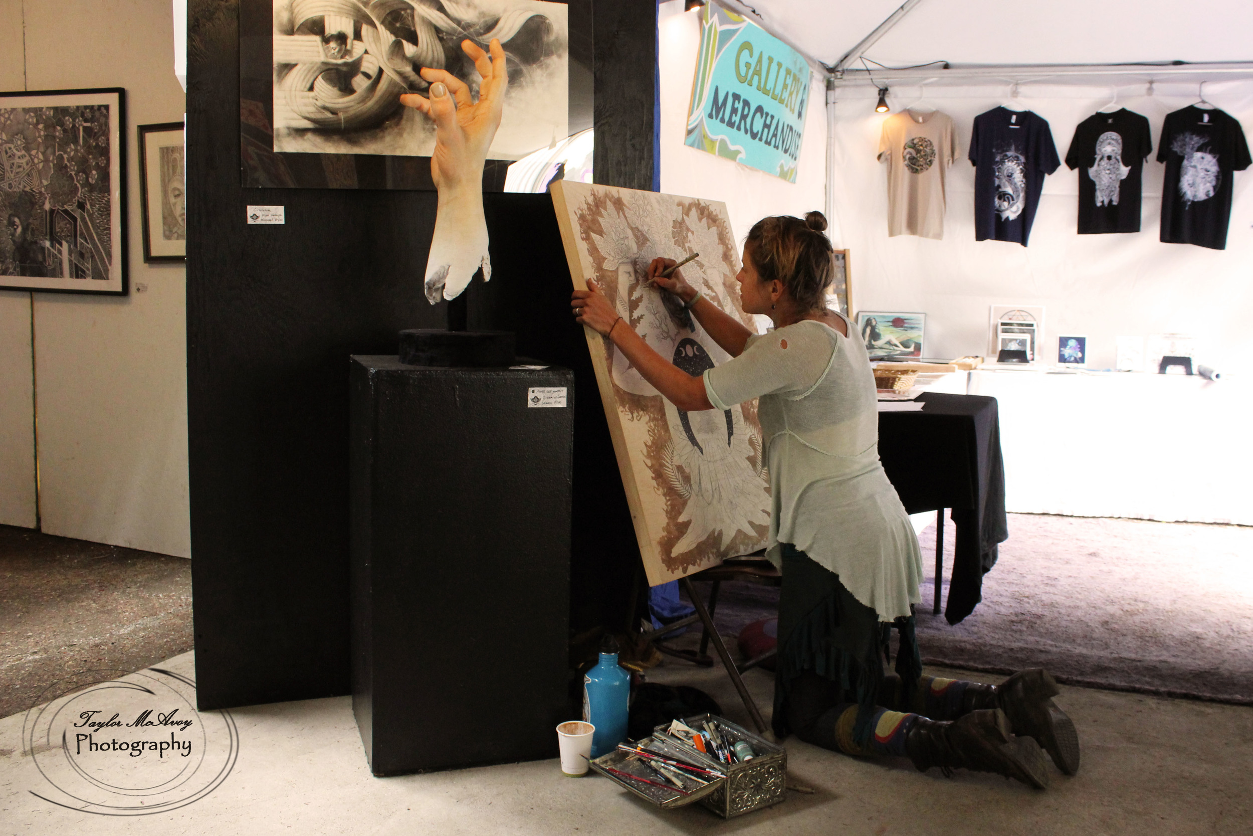 Artist Rose Drummond finishes a work in progress in the art tent full of paintings, abstract art and sculpture by Cascadian artists.