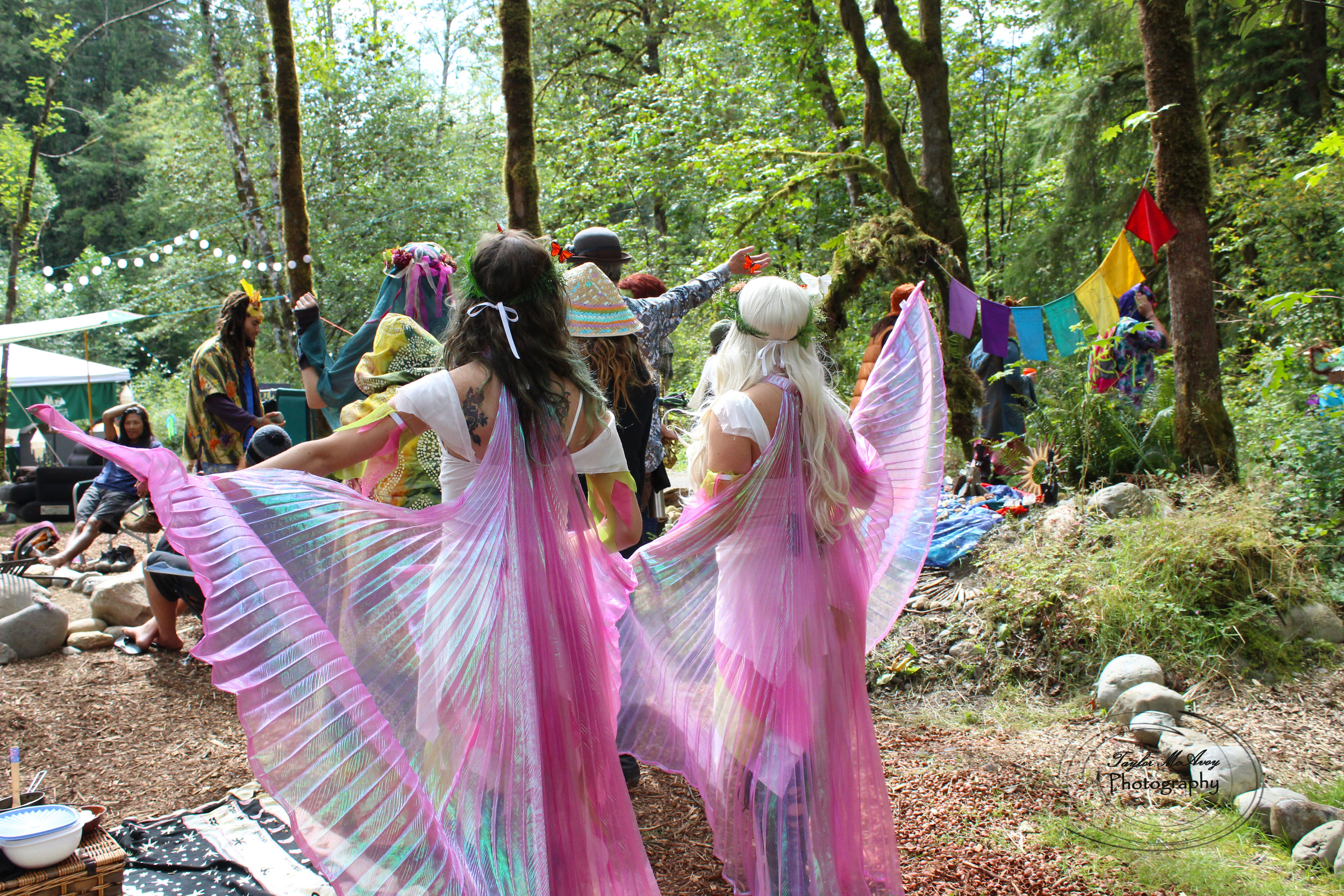 Faeries dance through the forest campsite in Mythica village before the community parade.