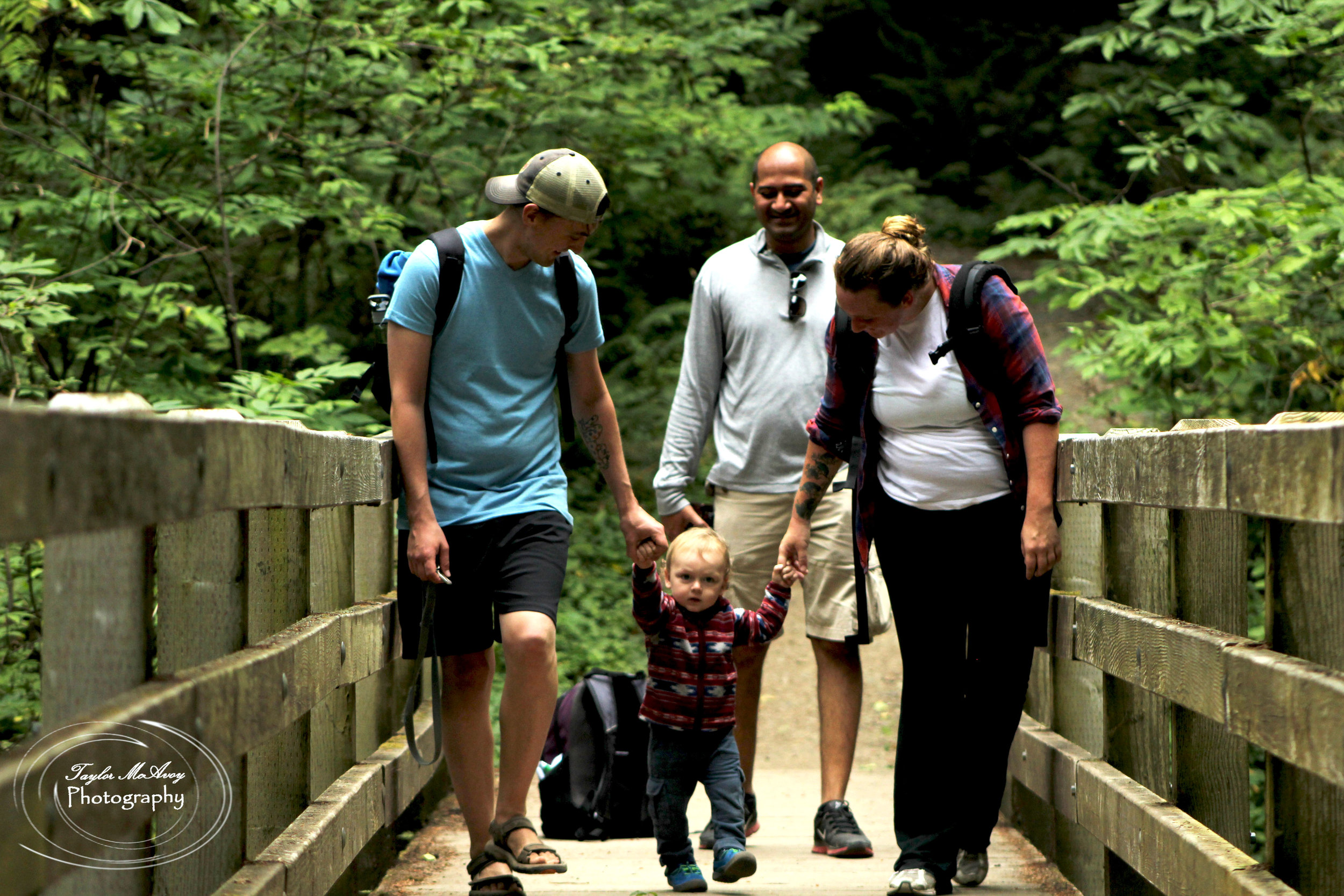 (From left to right) Andrew Schlosser, his son Atlas, AAditya Juwad, and Tephra Schlosser enjoy the view from the bridge of a small waterfall along the trail. Atlas enjoys the break from being carried to stretch his legs.