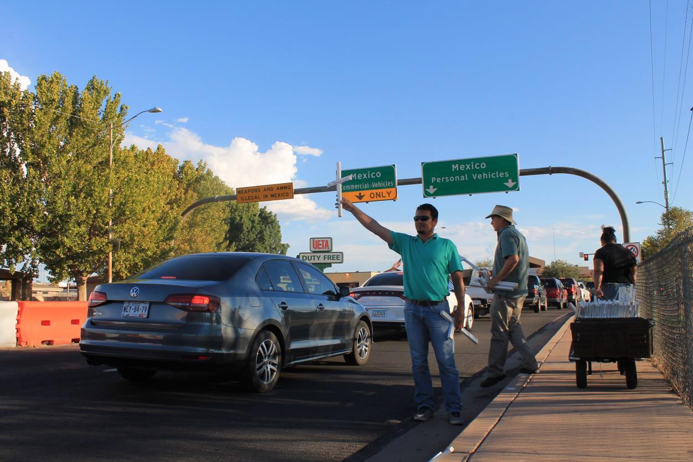 Miembros de Frontera de Cristo levantando cruces. Señales de tránsito indican la dirección a México. Al fondo, el Puerto de Entrada Raul H. Castro.  Foto: Jesús Francisco Quintero