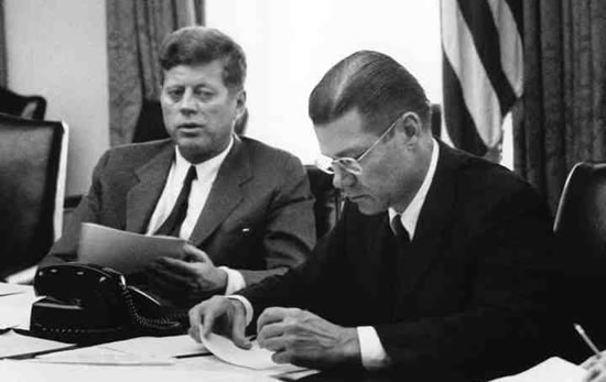 President Kennedy and Secretary of Defense McNamara in an EXCOMM meeting.  National Archives.