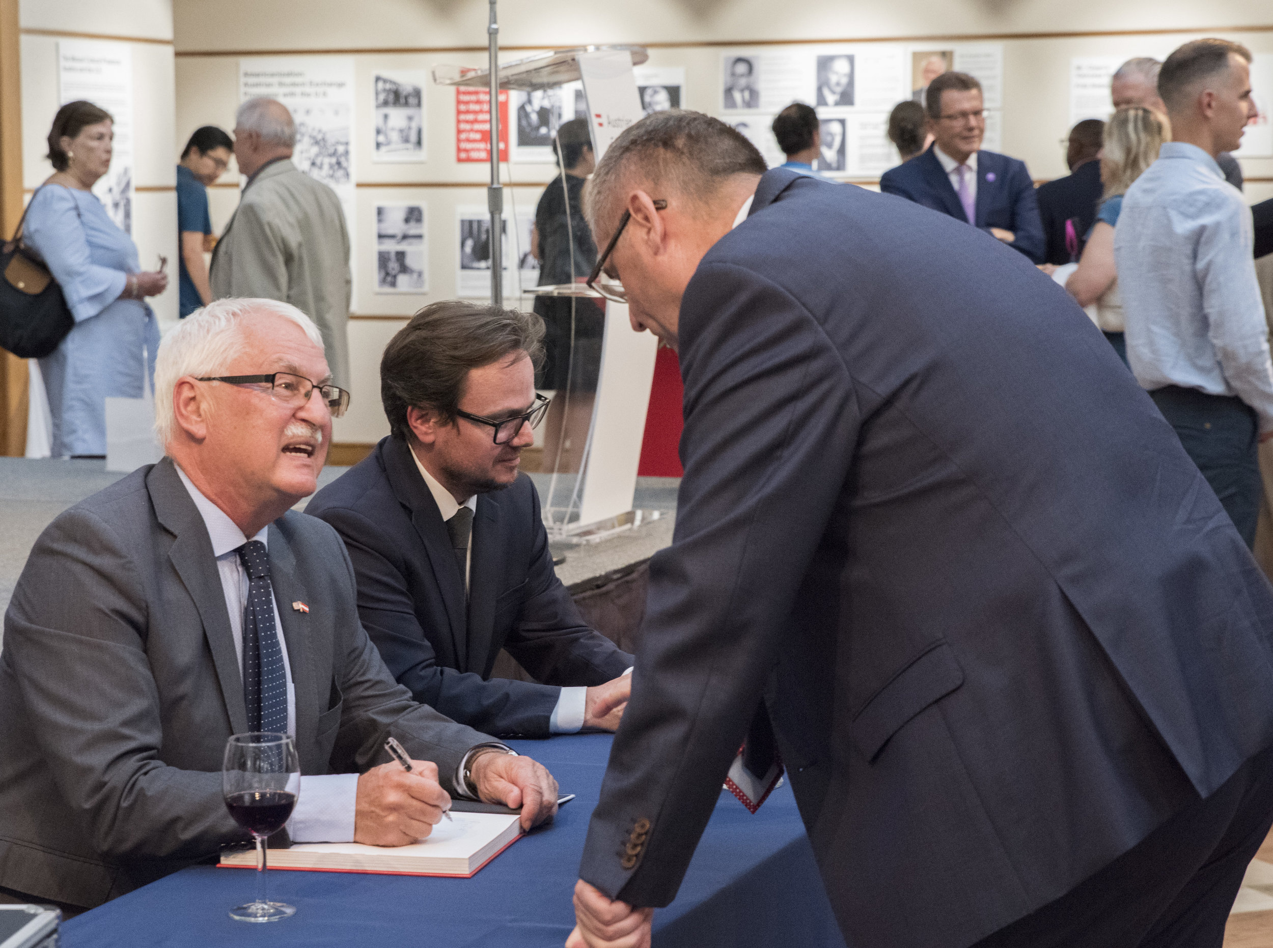Professor Günter Bischof (left) and co-author Dr. Hannes Richter sign books for guests.   Photo: Lenore Boulet