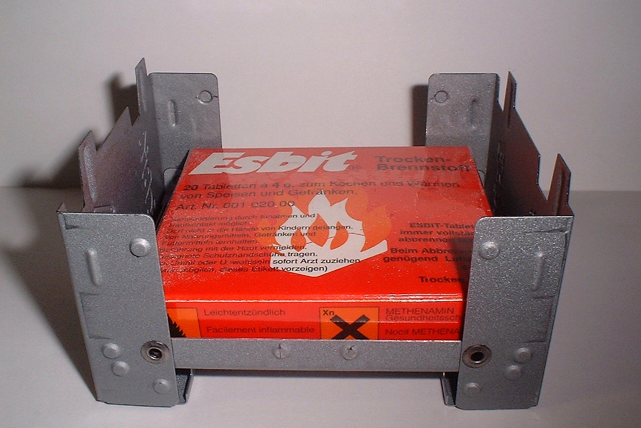 Esbit tablets in a solid fuel stove with a windbreak.