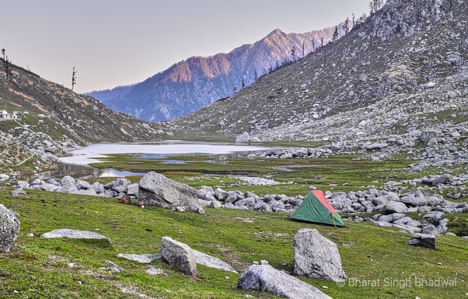Sunrise at Kareri lake. Our camp in the foreground on the East end of the lake. Shiv-Shakti temple on the left with Baleni pass lit in the background.