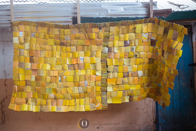 The building of an installation using cut up pieces of the yellow Kuffour gallons.