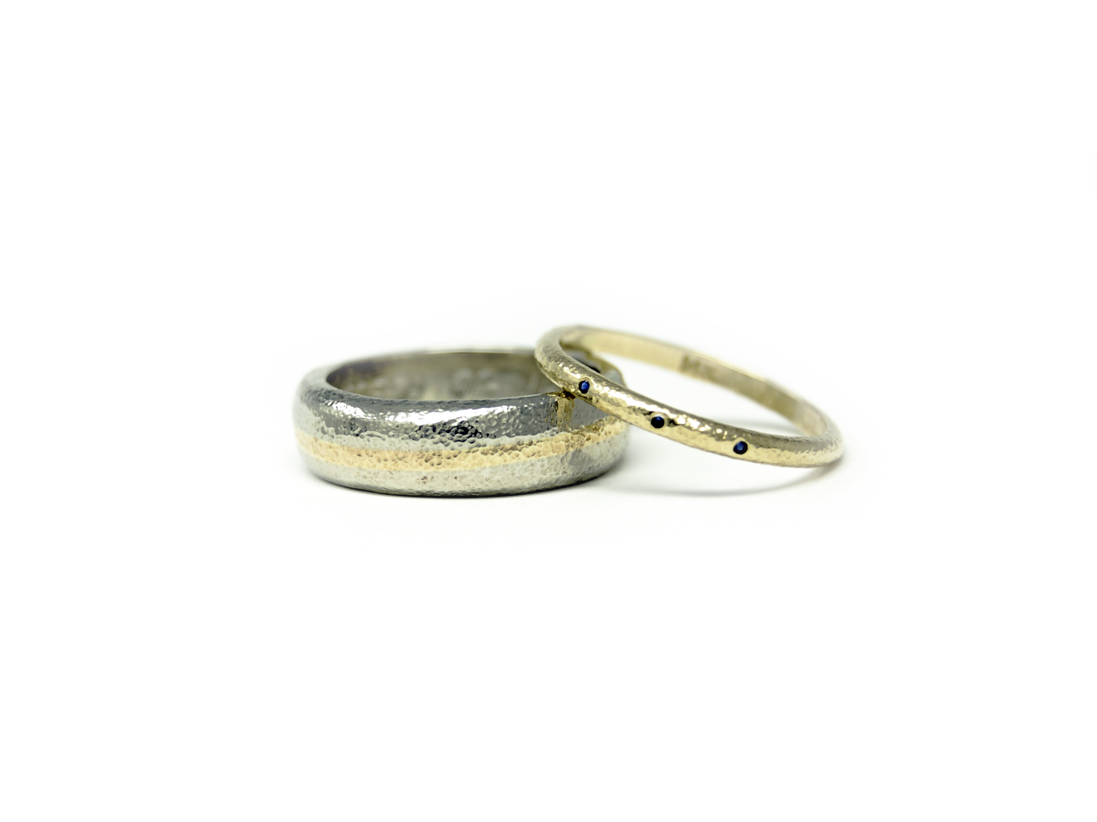 His + Hers pebble wedding bands. Hers is yellow gold featuring 1mm blue sapphires, his is white gold with a stripe of heirloom yellow gold up the middle!