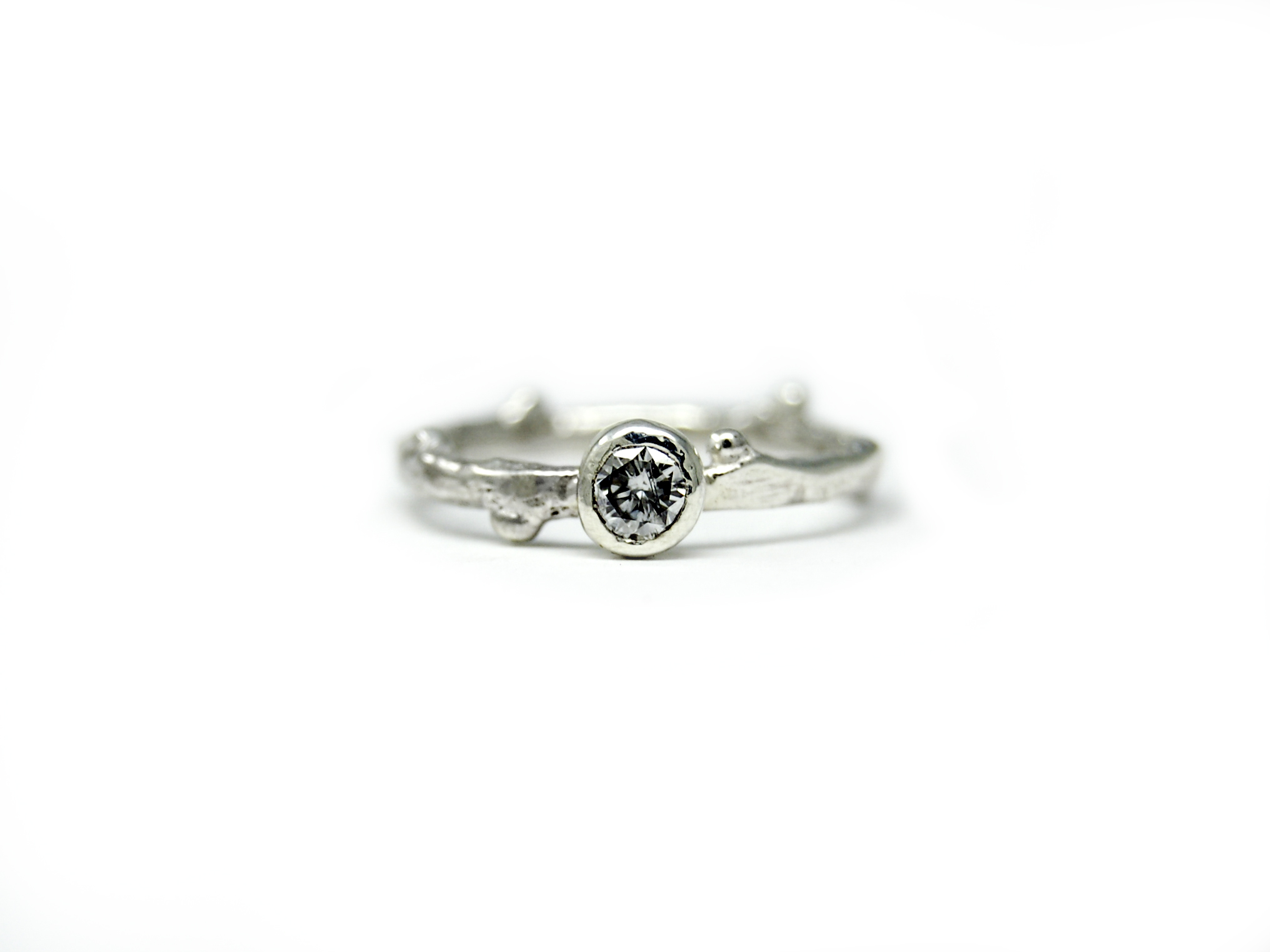 A custom sterling silver twig ring featuring our clients heirloom diamond
