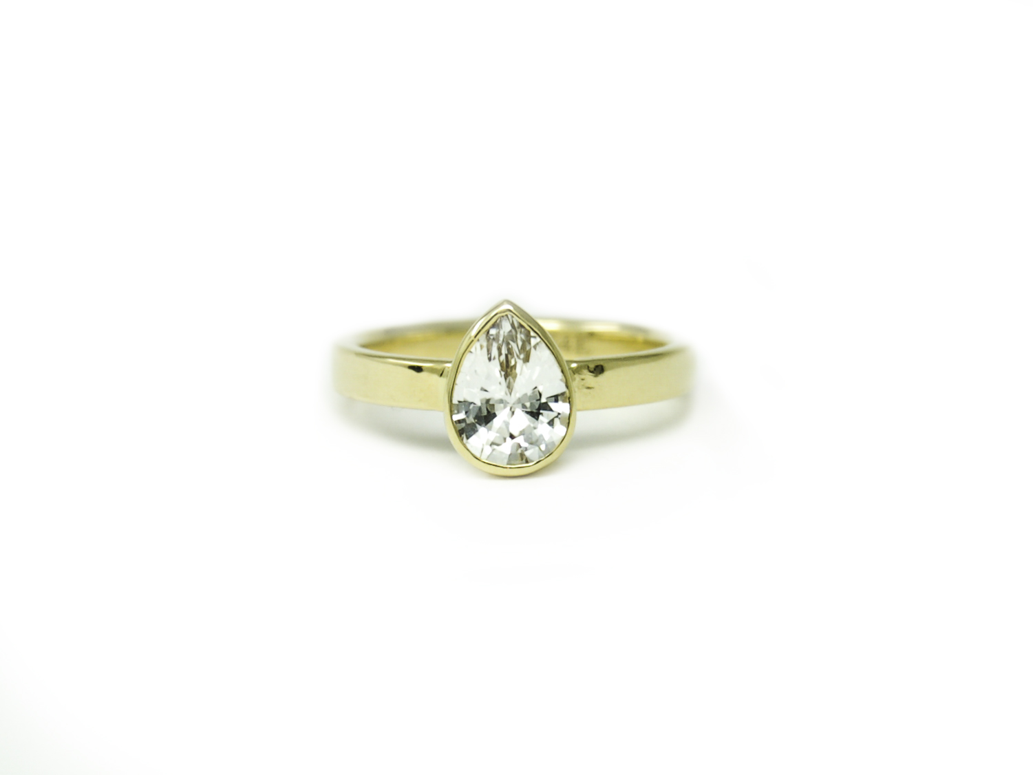 A recycled yellow gold engagement ring featuring a stunning white sapphire.