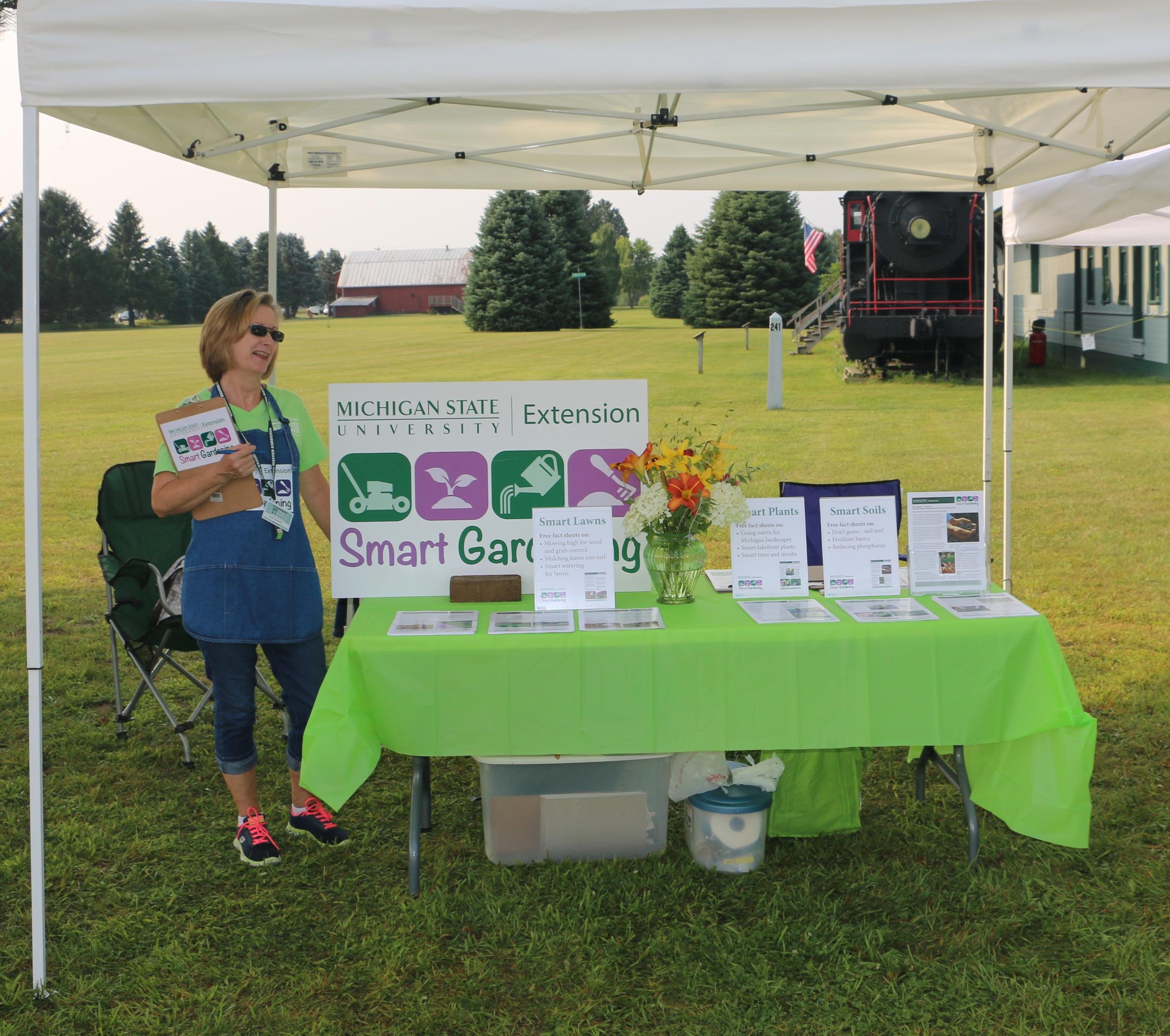 Master Gardener Smart Gardener Volunteer, Susan Bogardus with the Montcalm Area Master Gardener Association hosting a Smart Gardening booth at the Heritage Village Festival on the campus of Montcalm Community College.