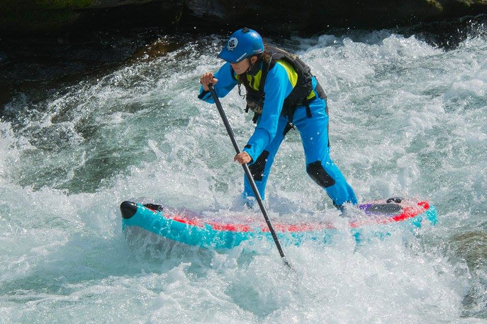 Nadia in full Flare Effect with her blue drysuit and blue helmet, paddling in the Pacific Northwest. Photo by Paul Clark
