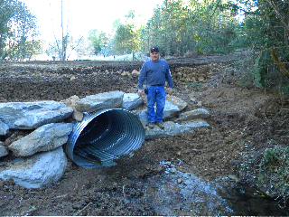 Bob Danielson standing by a culvert put in by Danielson Logging's road crew
