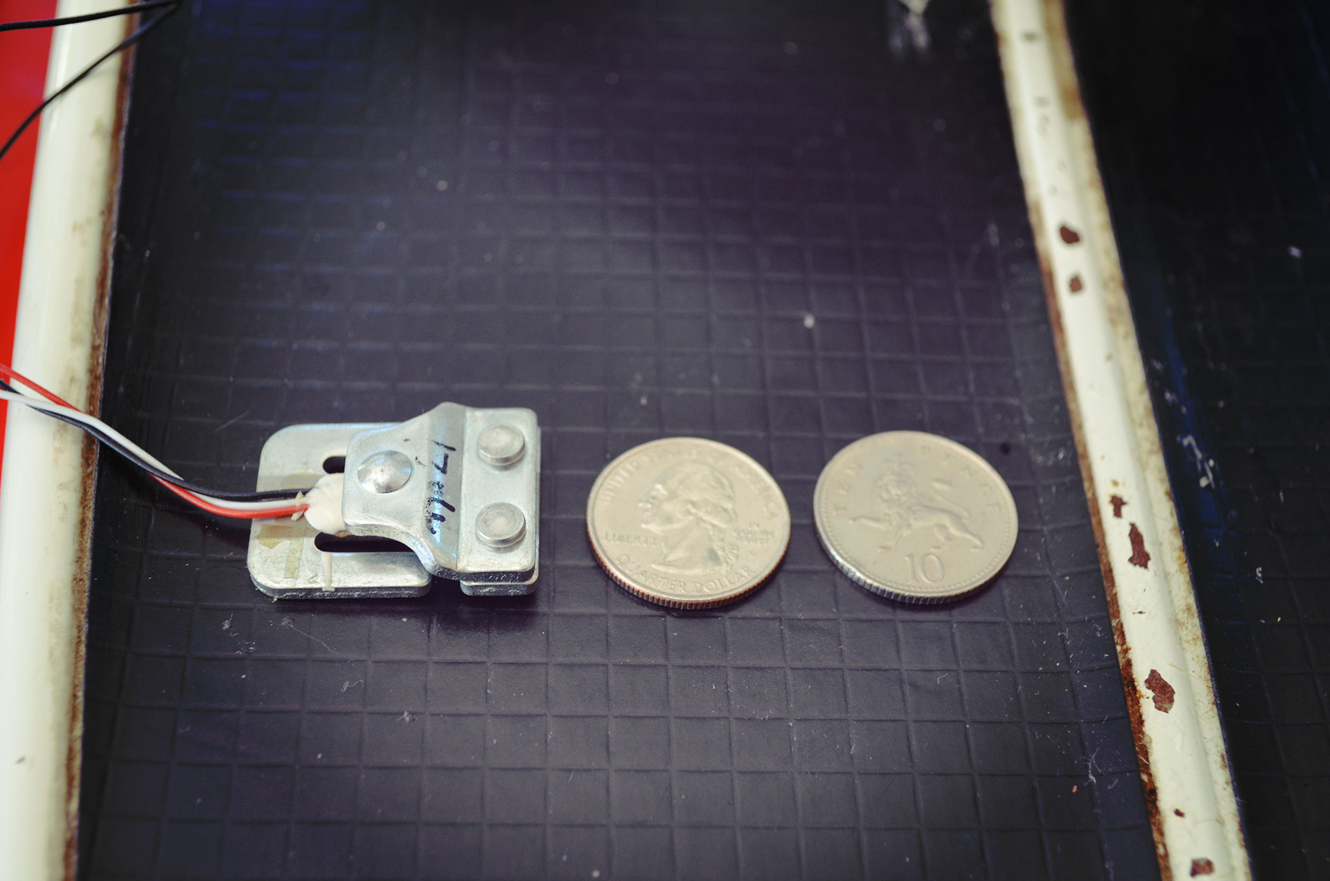 The load sensor I am testing next to a US Quarter and a Limey 10 p coin for scale reference. Weight is calculated by placing a load on the plate and measuring the change in resistance.