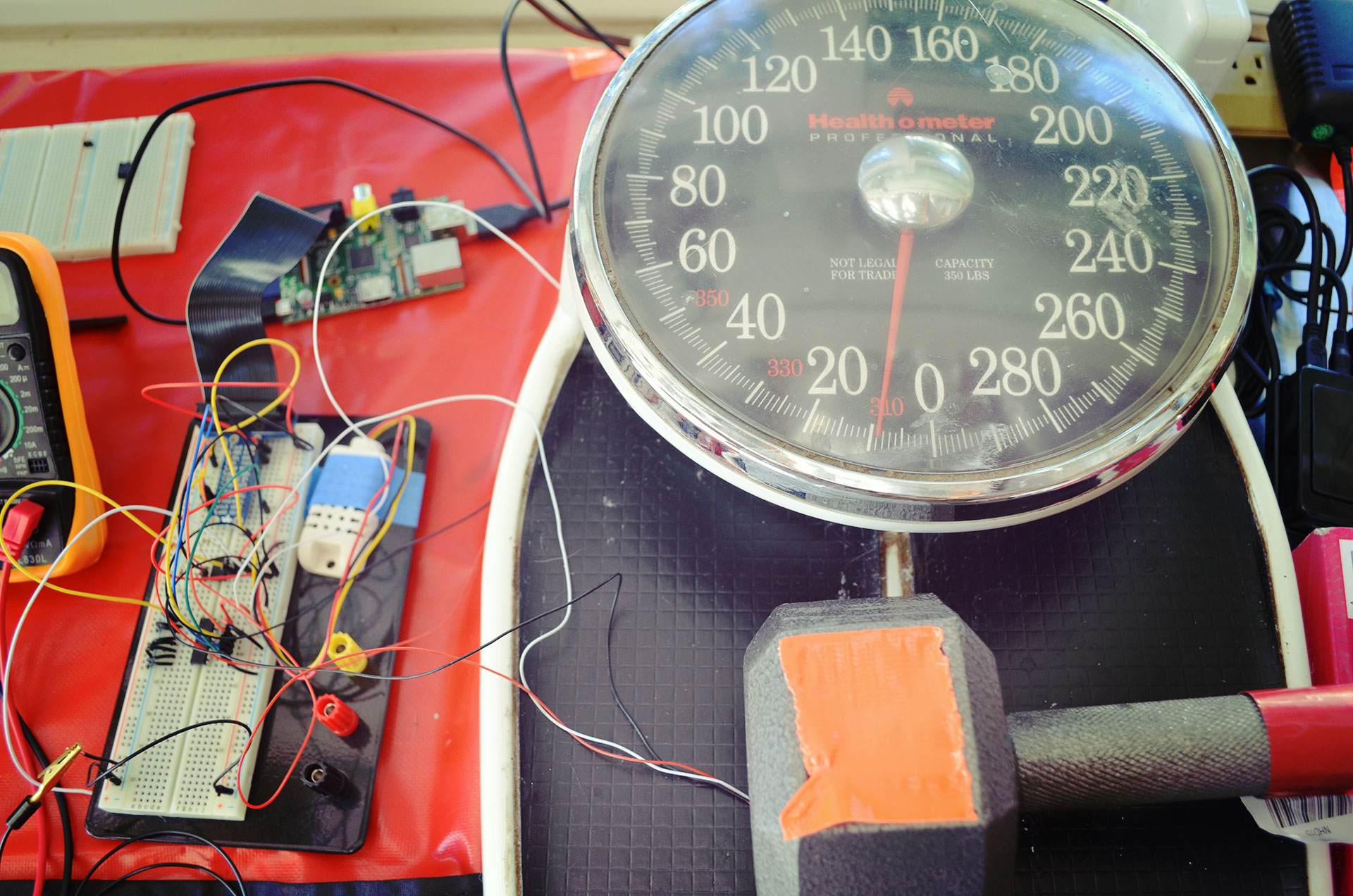The weight is placed on the sensor on top of an analog scale. We can see the current load on the sensor is about 9 lbs.