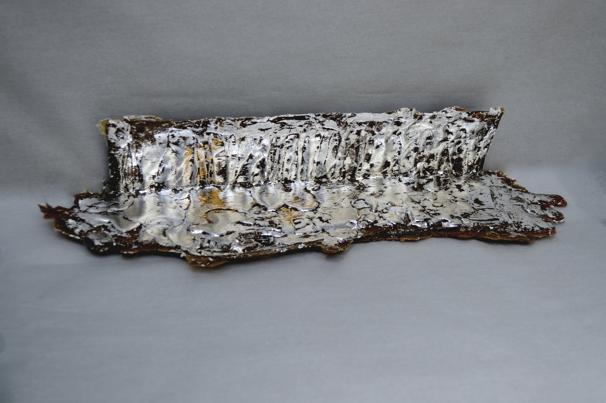 """Que Serra Serra?...will bee  ; site: title wall/floor foyer. material: matte aluminum, raw beeswax with tint, bee carcasses, silver leaf, 24k gold leaf. dimensions: 3.5"""" X 16.5"""" X 4.6"""", May 2019"""