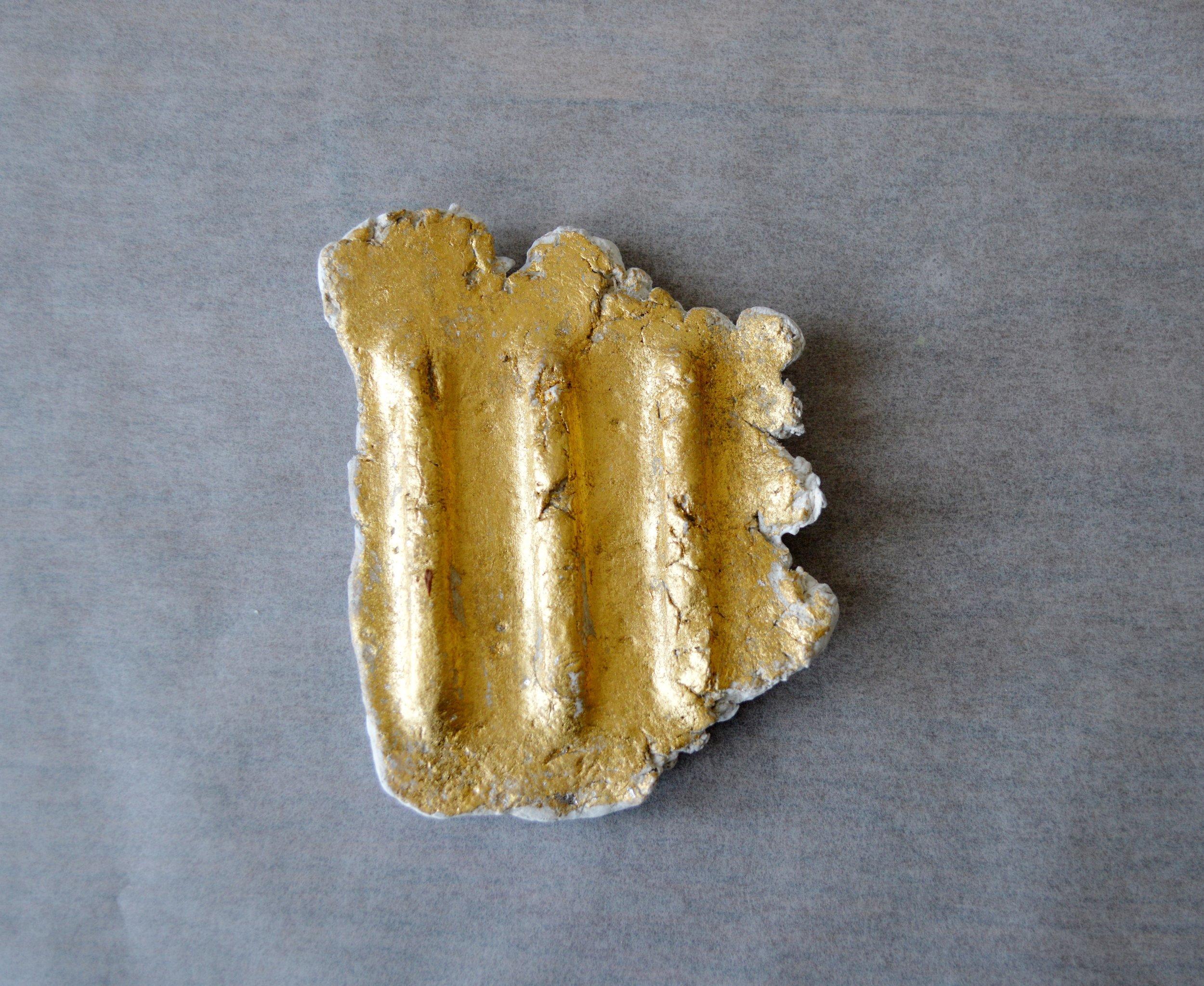 "3'  , site: anterior gallery. material: air dry clay, 24k gold leaf, graphite, gesso, matte medium. 5"" x 4"" x 0.5"", June 2019"