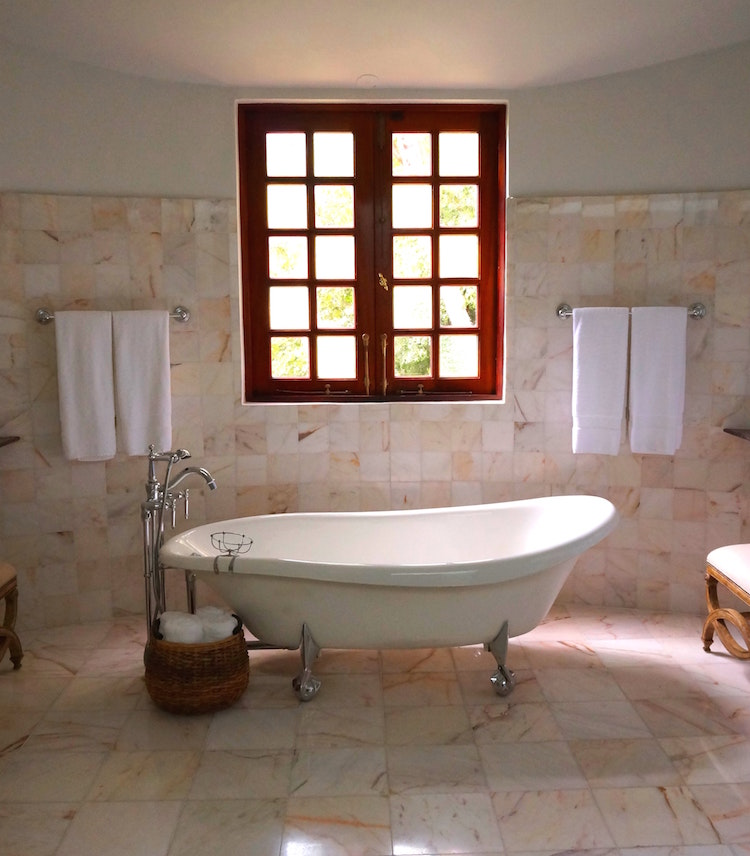 bathroom with marble tile and freestanding tub