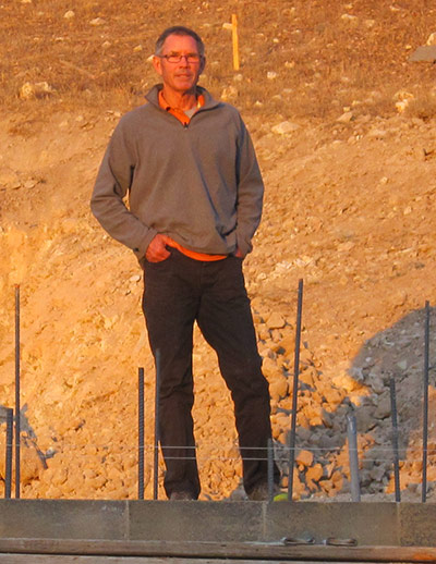 David Easton standing on an in-construction wall built of Watershed Block, which can be thought of as a third generation of  rammed earth technology. High pressure hydraulics consolidate select mineral compositions into mass produced masonry units.