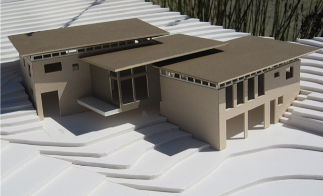 Architectural model for a  home designed using modularity principals and constructed from rammed earth Watershed Block . The dimensions of the structures were designed in multiples of the dimensions of the blocks to avoid waste from cutting blocks. The structure was designed with two primary structures connected by adjoining roofs to create a third living space between.