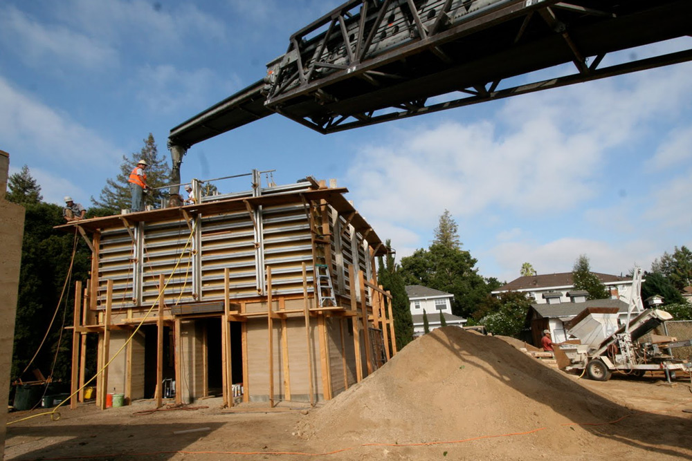 The repeating formwork has been hoisted up to build the rammed earth walls for the second story of this  modular rammed earth home in Mountain View .