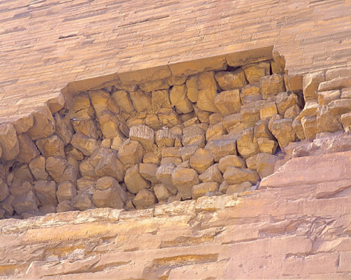 A gash in the side of one of the pyramids built by Senefru - the father of Khufu, who built the Great Pyramid - shows a combination of what appears to be irregularly cut quarried limestone blocks surrounded by tight jointed, cast-in-place geopolymer blocks. Image © Michel Barsoum, used with permission.