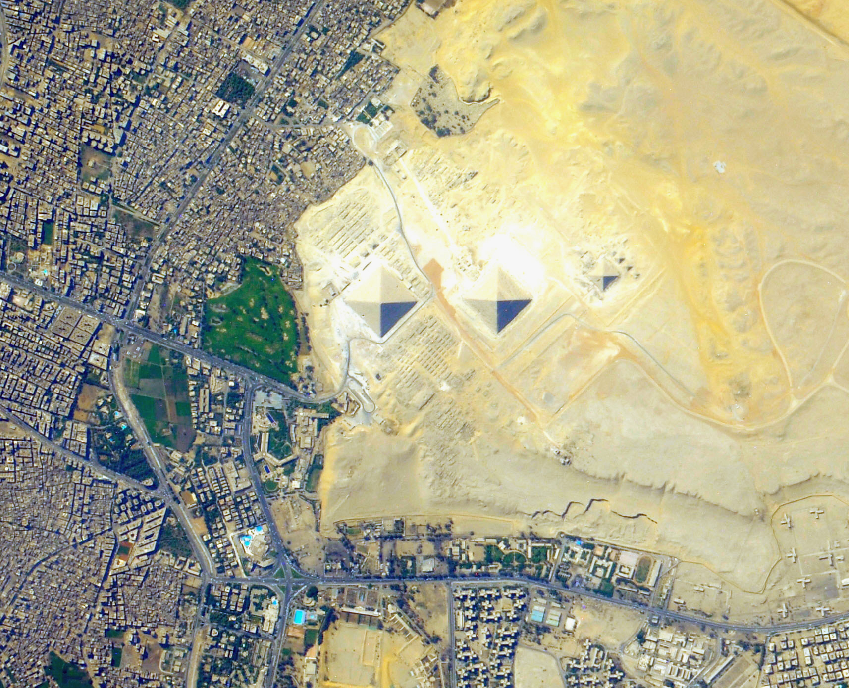 The Pyramids of Giza, as seen from the International Space Station. The pyramids are so large that they're clearly visible in a photograph taken with a hand-held consumer level digital camera from space. Their size is also overwhelming compared to the structures of modern Cairo. Public domain image courtesy of NASA / ISS Crew 032.