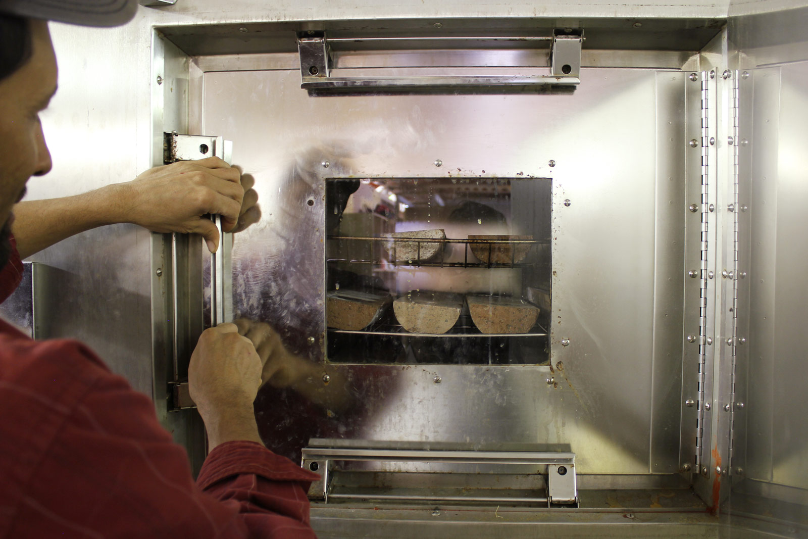 A technician checking test specimens in an environmental chamber. Curing conditions are fundamental to the success of Watershed Materials' geopolymer masonry production. In the factory or on-site production facility, masonry curing will take place on racks adjacent to the production facility. Another benefit of Watershed Materials geopolymer technology are relatively low curing temperature requirements; waste heat from hydraulic motors used by the production machinery can be reclaimed to marginally raise ambient temperatures for curing, supplemented by solar heating where necessary.