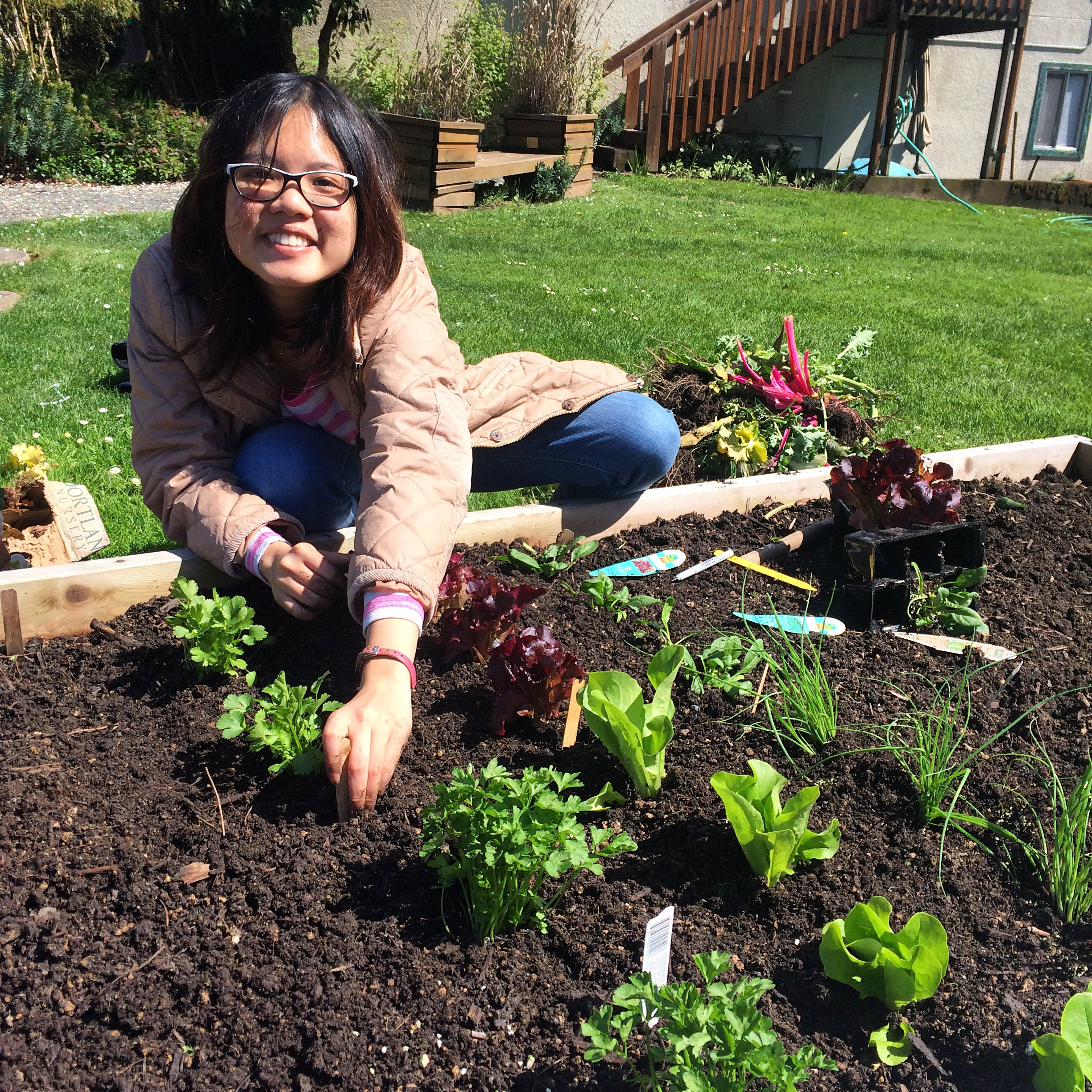 An international student from Thailand plants a familiar herb: Cilantro! at the OES Student Garden.