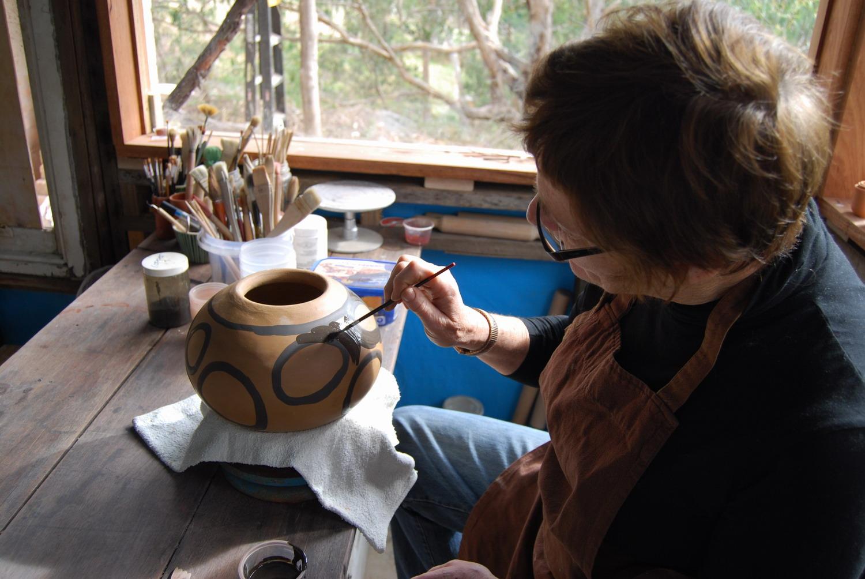 Ann Ferguson painting a small element.