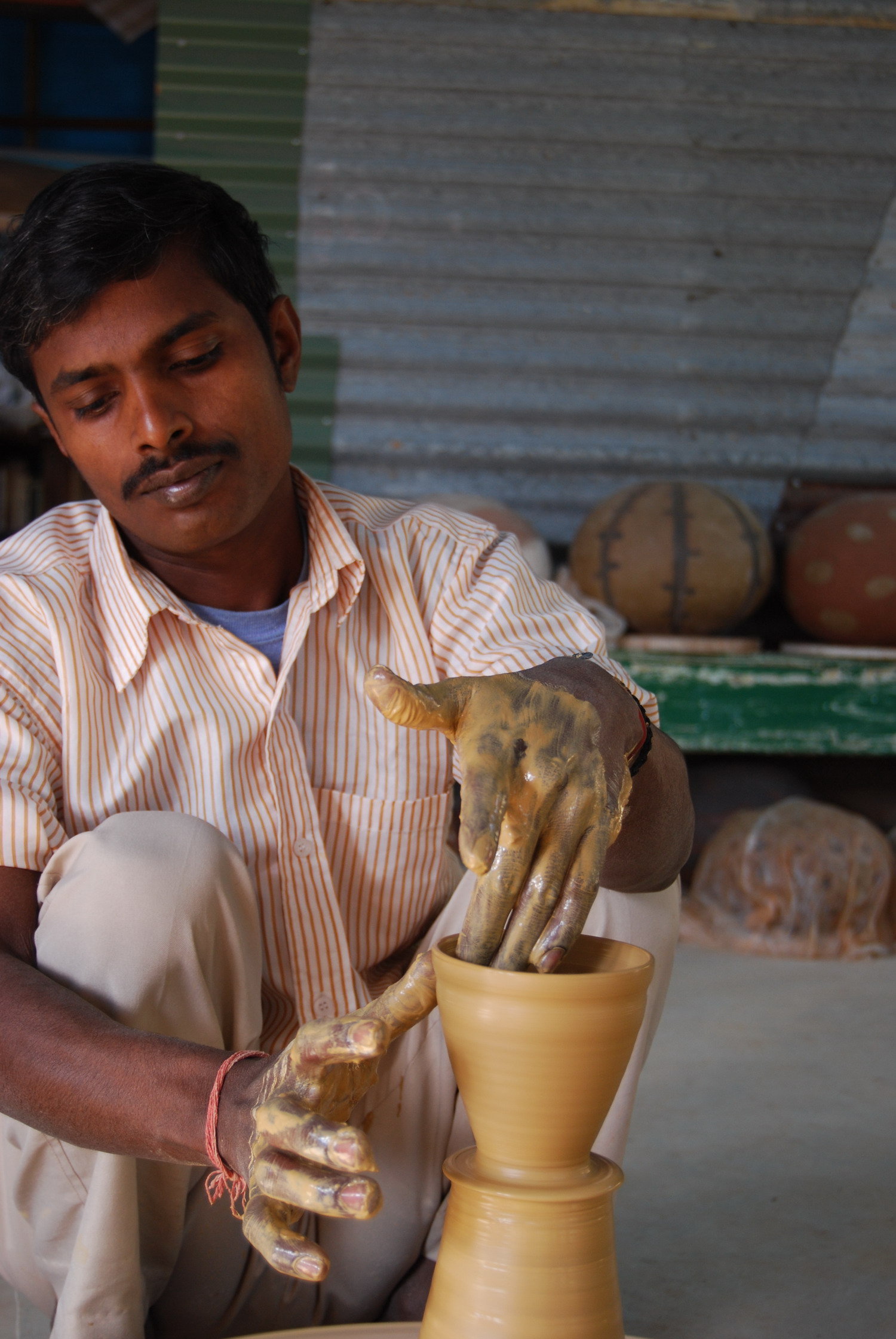 Banay Singh finishing lip on a chai cup.