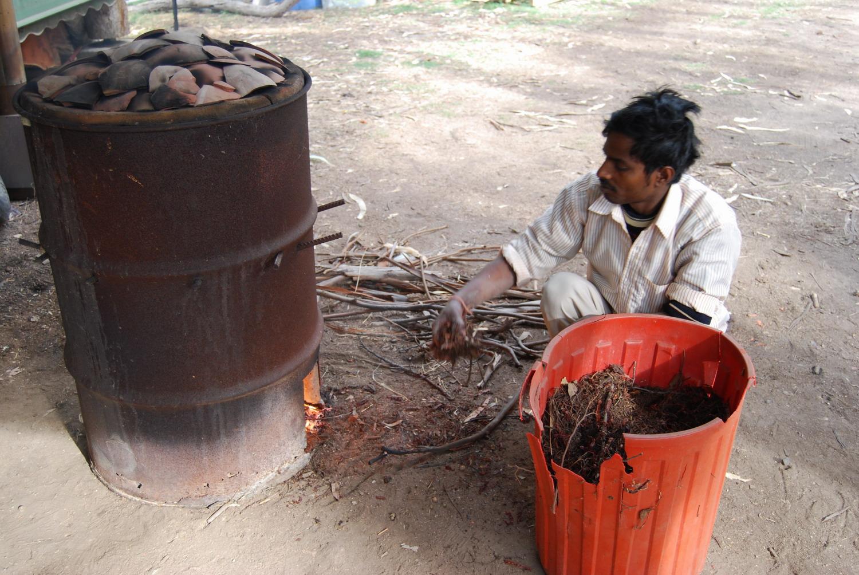 Banay Singh firing the drum kiln