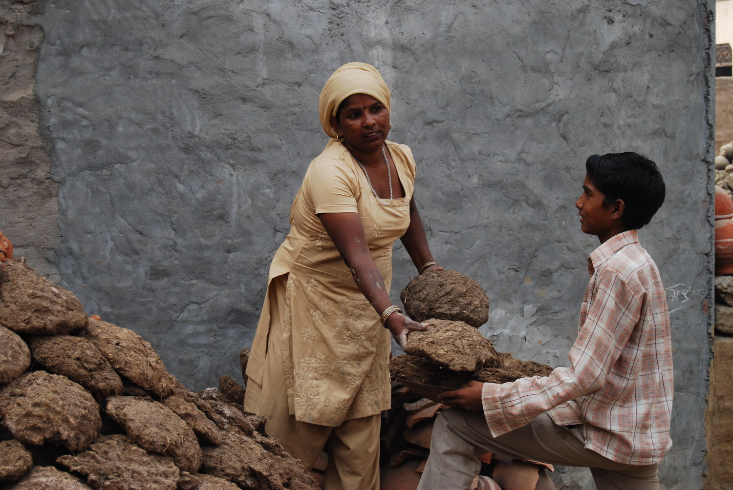 Vimla Devi and son covering the kiln with cow pats.