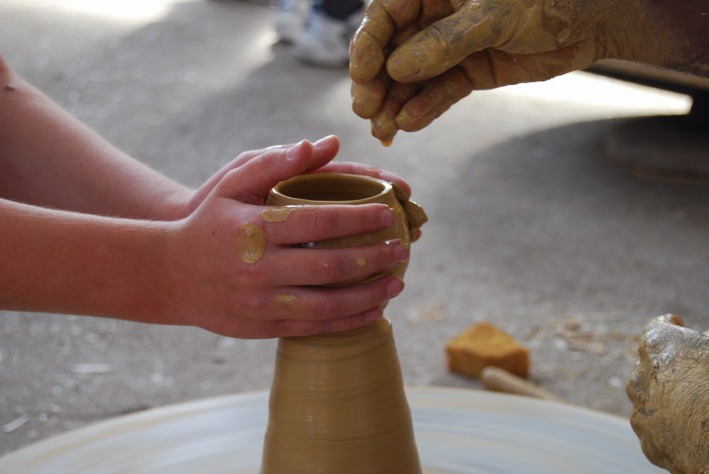 A student having their turn at making a small pot.