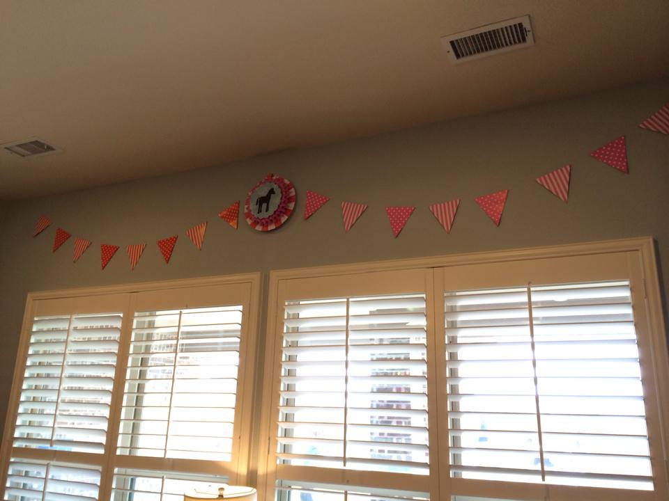 Oriental Trading has these striped and polka dot (double-sided) pennant banners in every color imaginable for around $3. I did two pennants here with a medallion I made in the middle. I also love the hanging paper fans from Oriental Trading, also super inexpensive. One of my tricks is to stack and hot glue the fans together-- so here I have a small one mounted on top of a medium. In the center I glued on a little horse silhouette that I made on the Cricut.