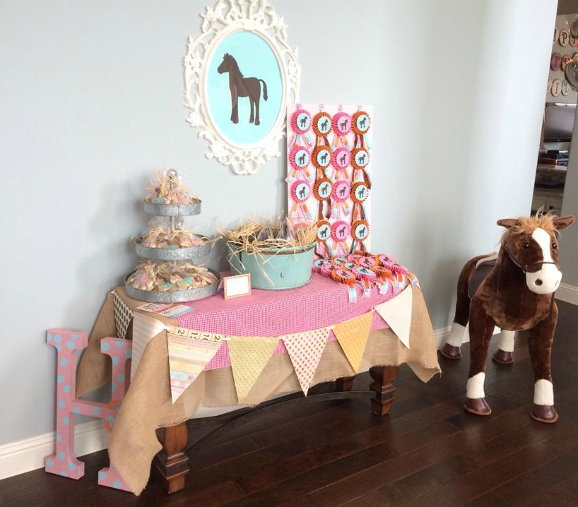 This favor table in my front entry was one of my main decor areas for this party. An heirloom painting generally hangs on the wall over this table, so it was a bit of a decision for me to decide to move it for the party, but I'm glad I did. The frame over this table is from Ikea and then I cut out the horse silhouette on my Cricut. The horse ribbons on the right are all made out of paper and ribbon and I made them all-- again using my Cricut for the horse silhouette on top. I just love how this little space came together and set the tone for the whole party. I also made the paper pennant banner on the front of the table with my Cricut as well.