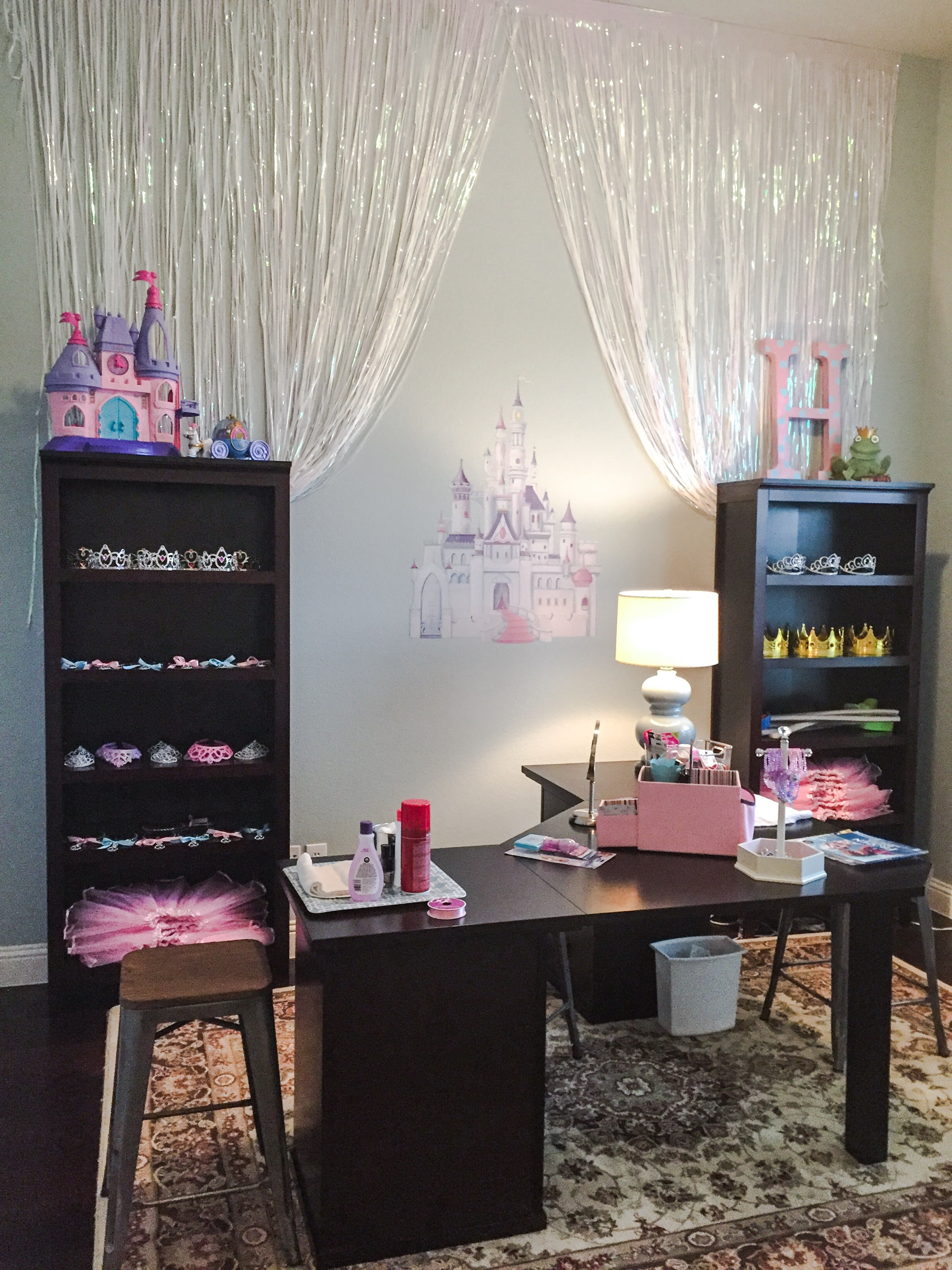 My husband's office, mostly emptied out and turned into Bibbidi Bobbidi Boutique!  We had a manicure/ nail painting station, makeup station and hair station.  The girls also all got to pick out one of the princess body stickers (from Party City and super cute!).  They all got to pick out crowns or tiaras, tutus and I had the most adorable handheld mirrors for them all in addition to bracelets, necklaces and rings! This space is right beside our ballroom, so it flowed really well together!